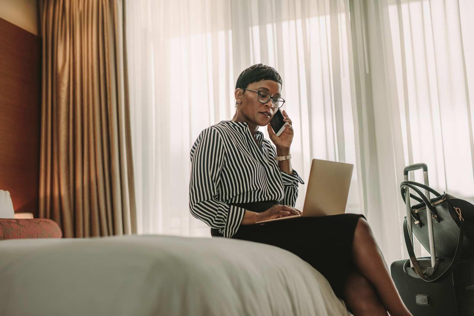 Mulher de negócios feliz e confortável numa cama de hotel