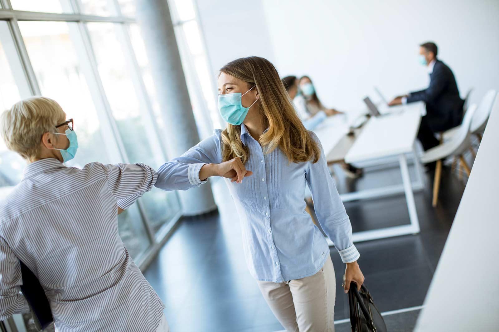 Duas mulheres de negócios de máscara covid a comprimentarem-se numa sala de reuniões