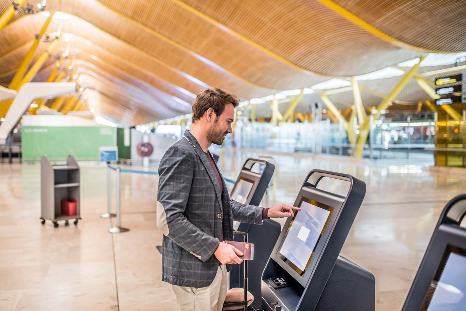 Happy man using the check-in machine at the airport getting the boarding pass