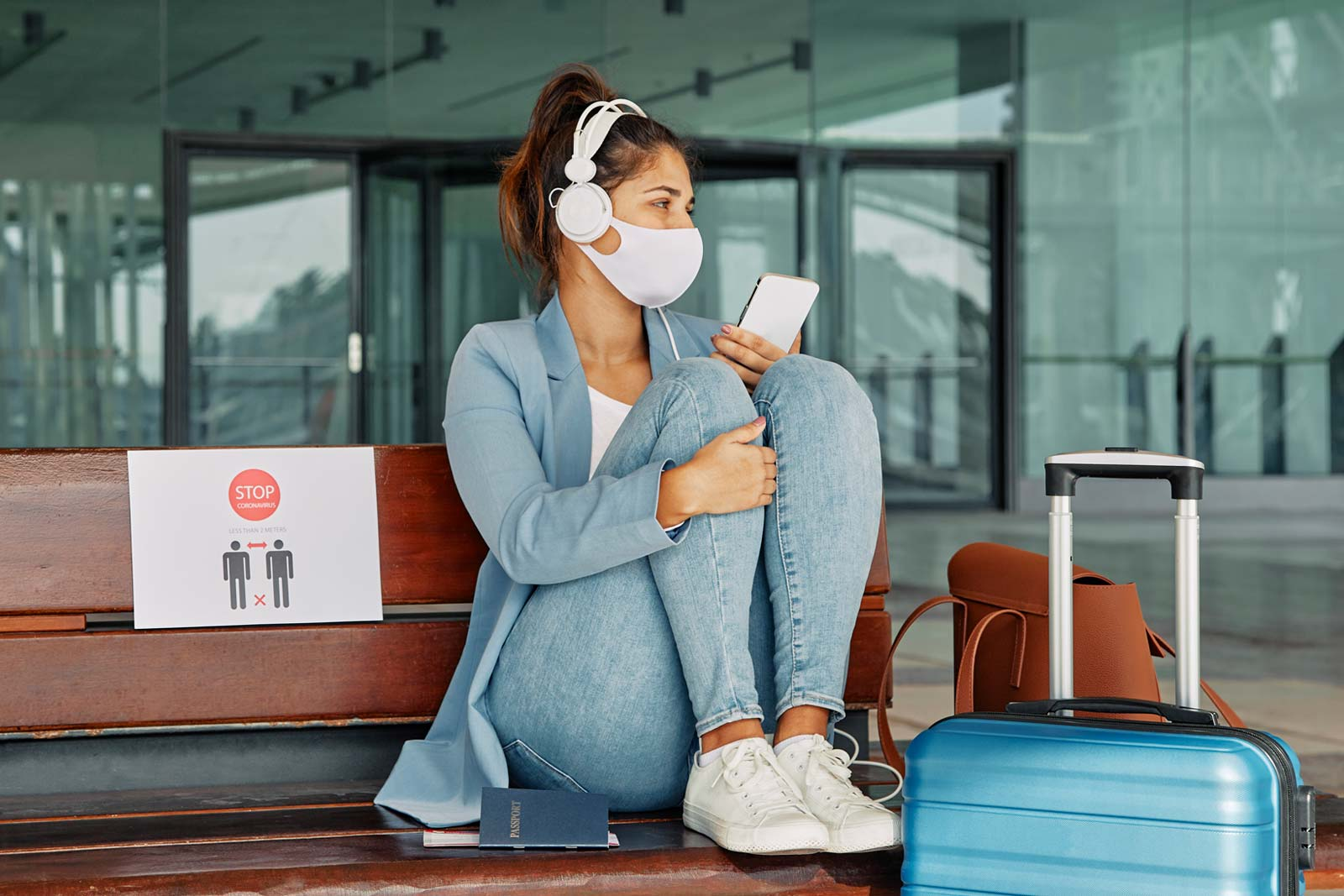 Woman with COVID-19 mask and headphones in the airport during pandemic