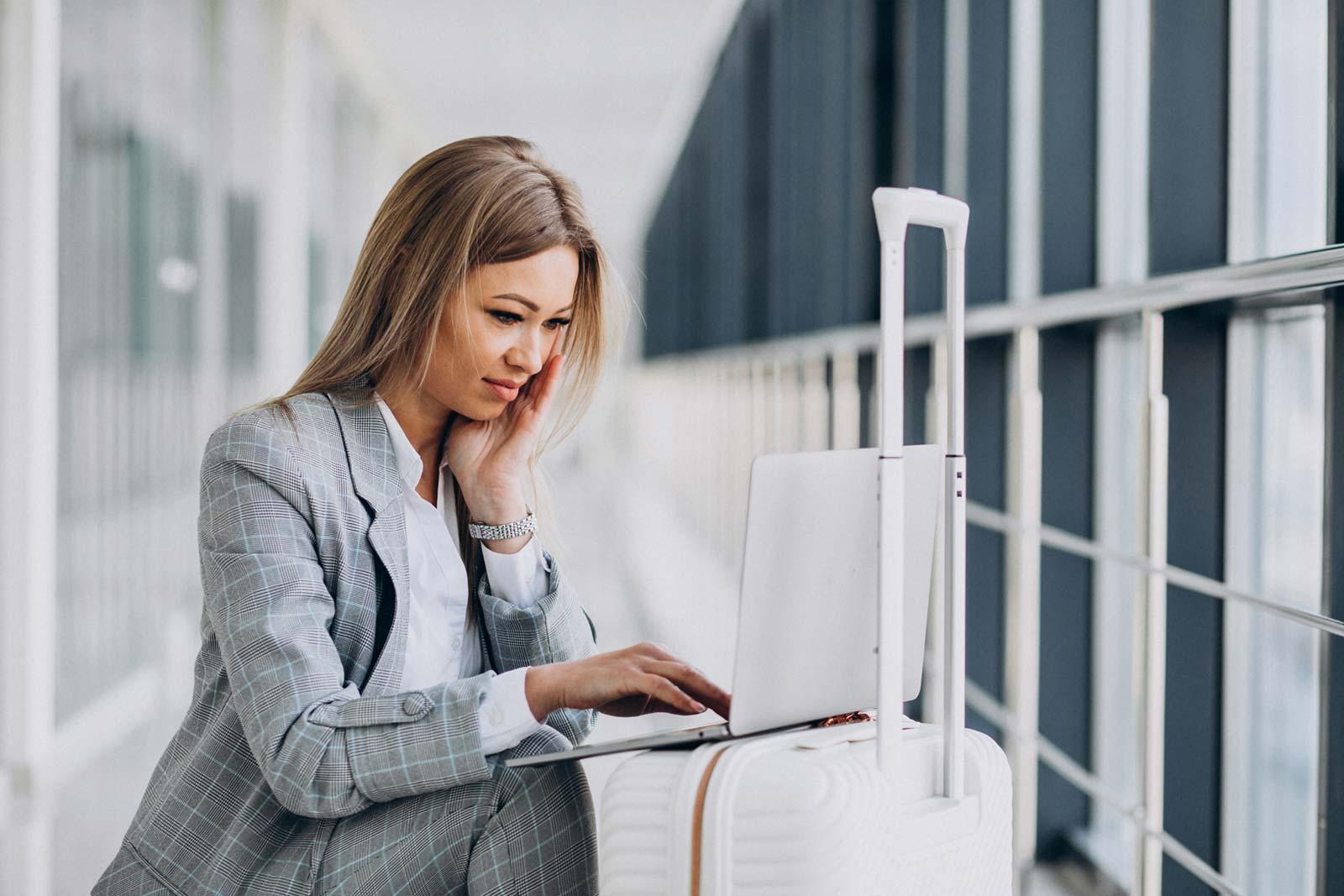 Mulher de negócios com uma mala de viagem, reservando um voo no laptop no aeroporto