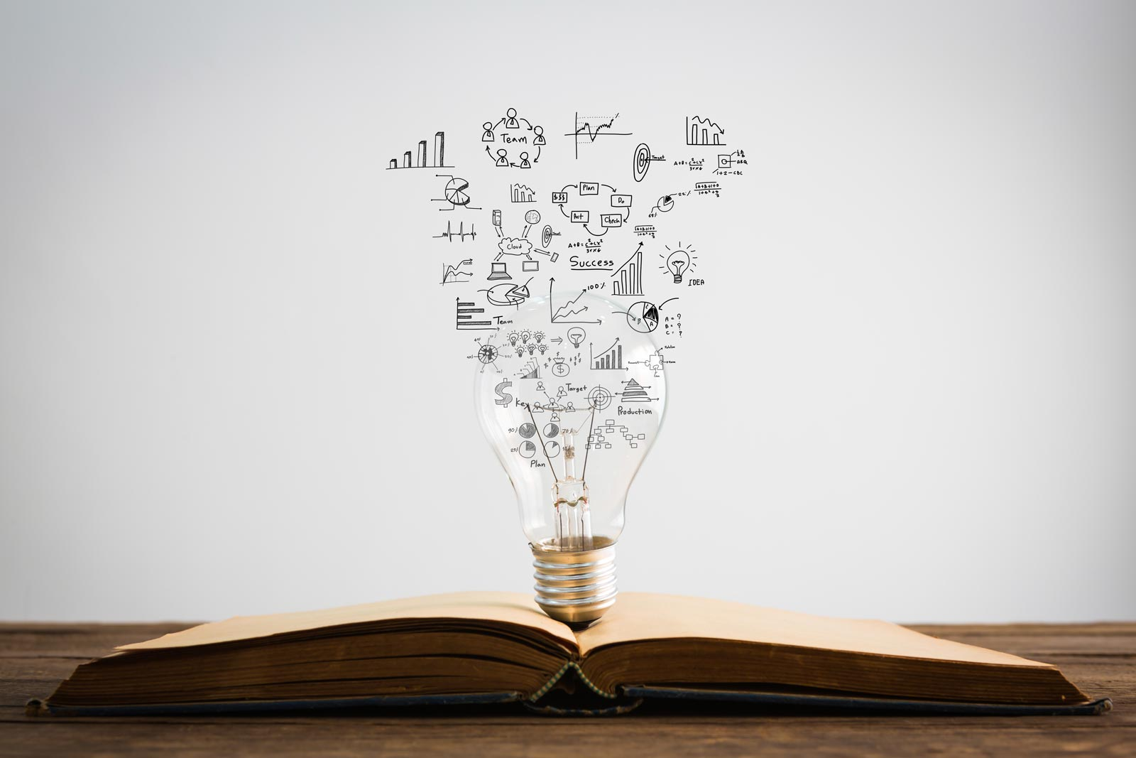 Symbols come out of a bulb on top of a book