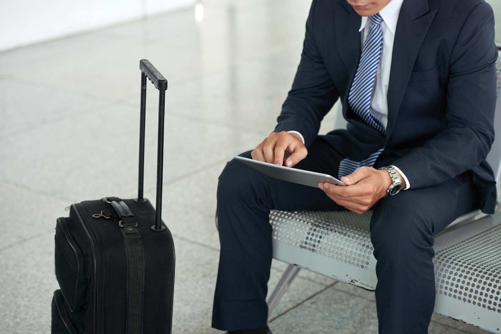 Homem de negócios usando o tablet no aeroporto