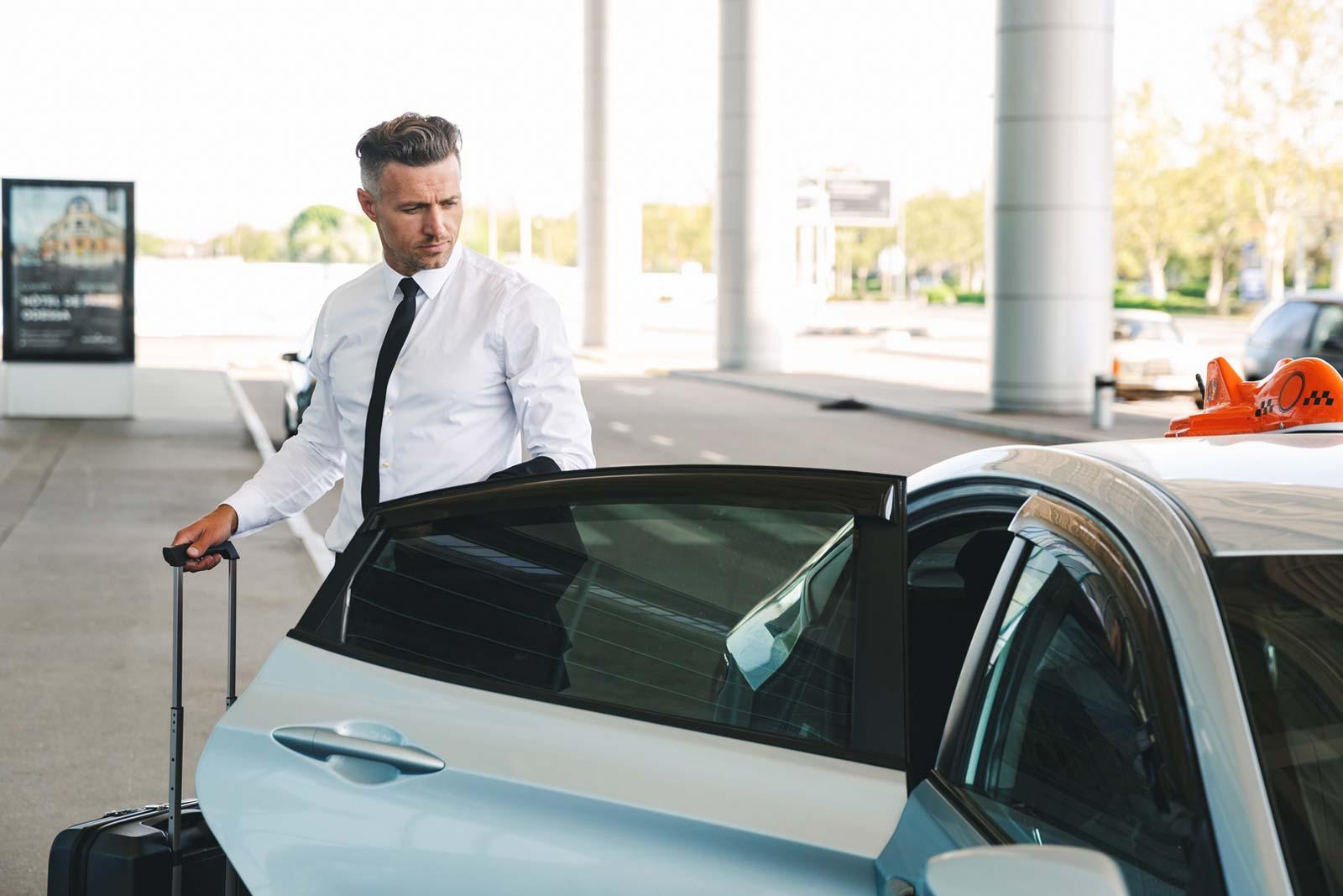 Homem de negócios a entrar em taxi no aeroporto