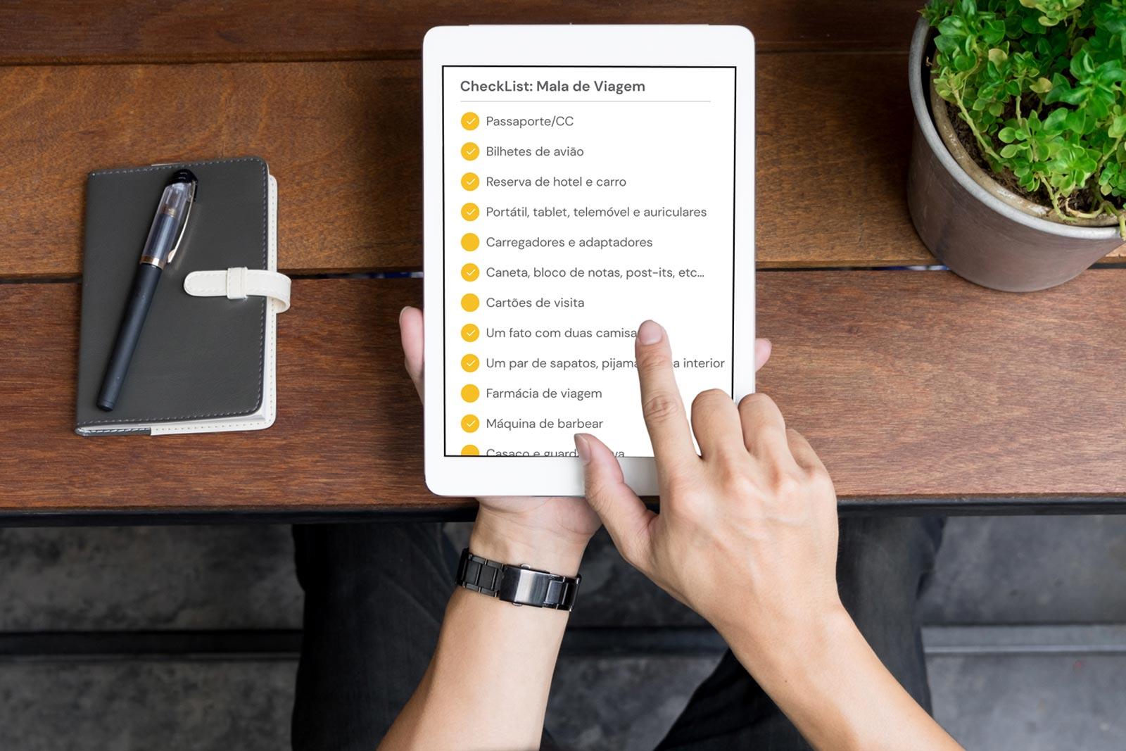 Homem a usar um tablet para organizar as coisas que precisa de levar na sua viagem de negócios