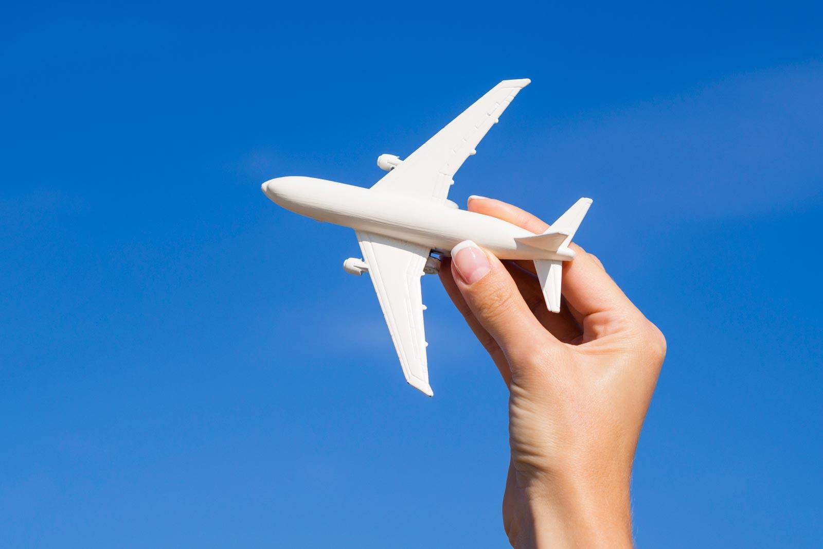 Mão feminina segurando um modelo de avião, num céu azul
