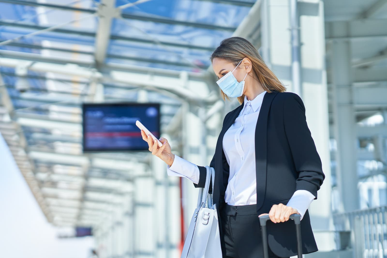 Mulher de negócios numa estação de comboios a consultar o smart phone