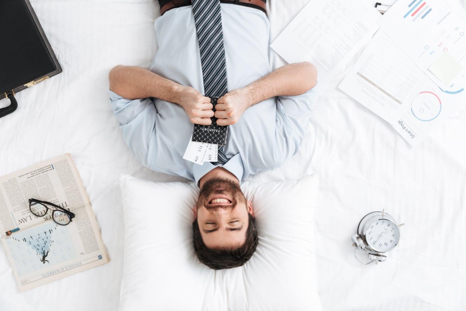 Jovem empresário sorridente deitado numa cama de hotel com o passaporte nas mãos