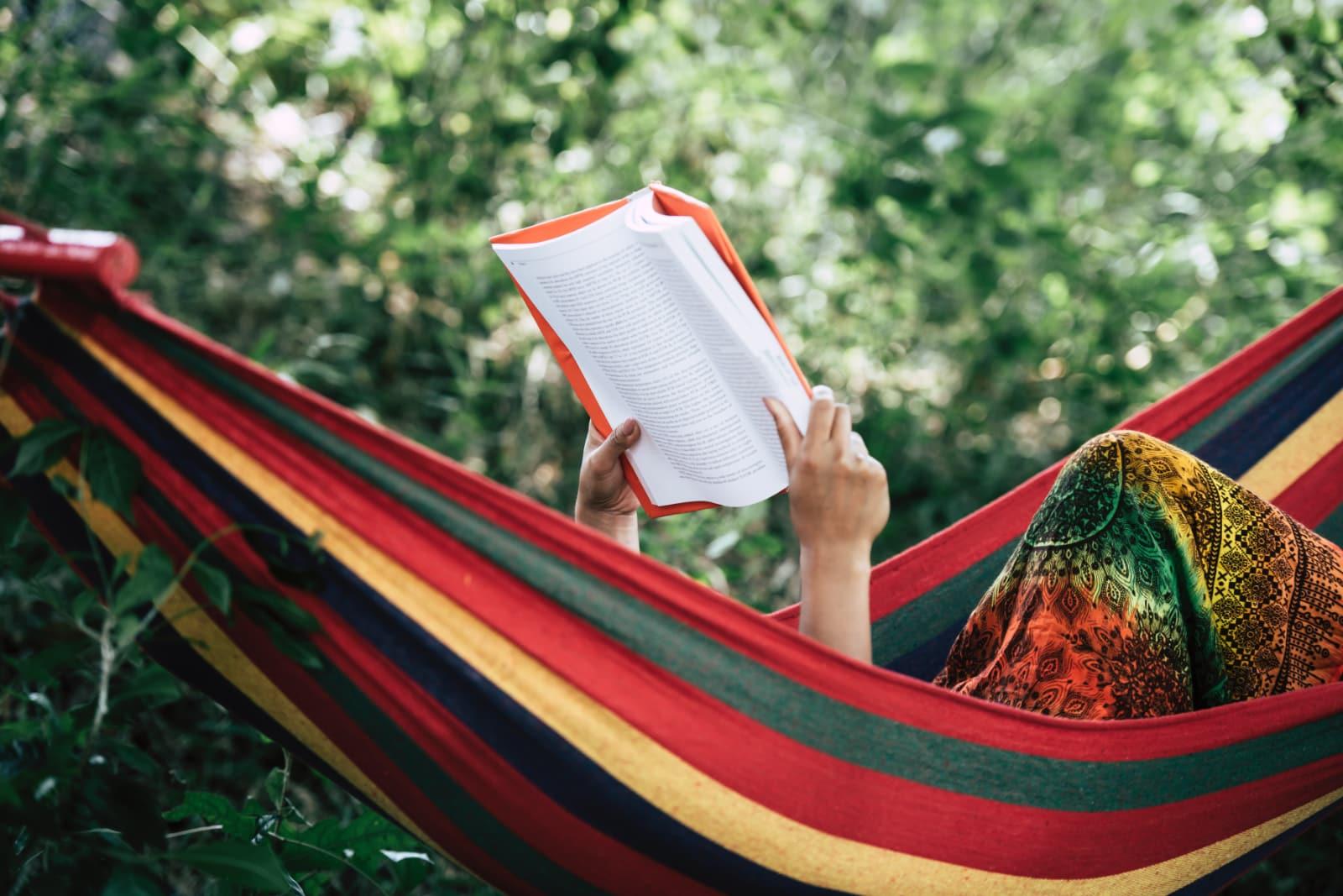 Mulher a ler um livro numa cama de rede no meio da natureza