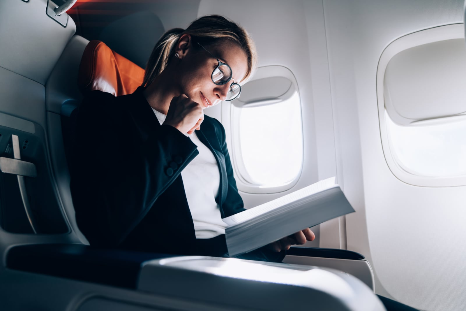Woman reading a book during her flight